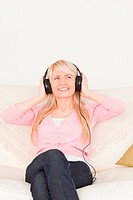 Beautiful female listening to music on her headphones while sitt