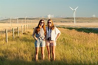 Two sisters, 16 and 20, stand in a field in southern Alberta, Canada
