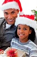 Portrait of an Afro_American father and son holding a Christmas gift