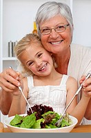 Happy grandmother eating a salad with granddaughter