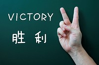 Victory gesture on a blackboard background