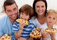 Portrait of family eating pizza in living_room