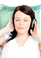 Relaxed young woman listening music with headphones