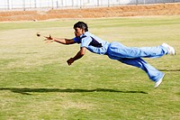 A fielder catching a cricket ball