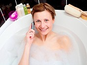 Beautiful woman talking on phone in a bubble bath
