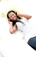 Cheerful woman listening music with headphones lying on a sofa