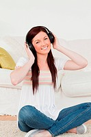 Good looking red_haired woman listening to music with headphones