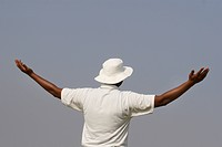 A cricketer raising his both hands wide