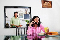 Mother cooking in kitchen and daughter having breakfast