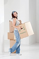 Young woman carrying cardboard box, smiling, portrait