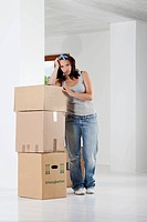 Young woman leaning on cardboard boxes, portrait (thumbnail)