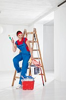 Germany, Bavaria, Young woman leaning on step ladder with paint equipments, smiling, portrait