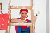 Germany, Bavaria, Young woman standing on step ladder with paint brush