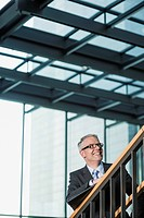 Germany, Stuttgart, Businessman moving up on office staircase (thumbnail)