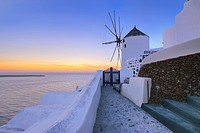 Greece, View of Oia village with traditional Greek windmills in sunset at Santorini