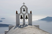 Greece, Bell tower of whitewashed church in Imerovigli, sea in background at Santorini