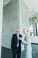 Germany, Stuttgart, Business people in office lobby, smiling