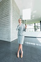 Germany, Stuttgart, Businesswoman standing with blank signs in office lobby