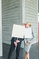 Germany, Stuttgart, Business people holding blank signs in office lobby, kissing