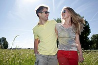 Germany, North Rhine Westphalia, Duesseldorf, Couple walking in grass, smiling