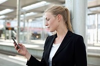 Germany, North Rhine Westphalia, Duesseldorf, Young woman using smart phone at station (thumbnail)