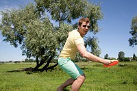 Germany, North Rhine Westphalia, Duesseldorf, Mid adult man playing with frisbee, smiling