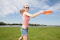 Germany, North Rhine Westphalia, Duesseldorf, Young woman playing with frisbee, smiling