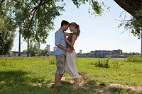 Germany, North Rhine Westphalia, Duesseldorf, Couple embracing on grass, smiling