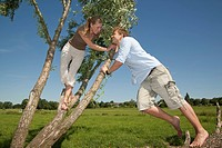 Germany, North Rhine Westphalia, Duesseldorf, Couple playing with tree, smiling