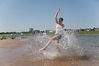 Germany, North_Rhine_westphalia, Duesseldorf, Young woman splashing in water