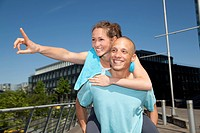 Germany, North_Rhine_Westphalia, Duesseldorf, Young man giving piggy back ride to woman