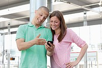 Germany, North_Rhine_Westphalia, Duesseldorf, Young couple watching mobile phone
