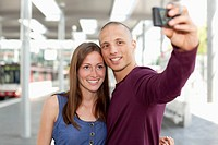 Germany, North_Rhine_Westphalia, Duesseldorf, Young couple photographing self with smart phone