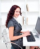 Smiling businesswoman working in office with a computer