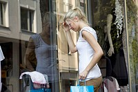 Germany, North Rhine Westphalia, Cologne, Young woman at window shopping (thumbnail)