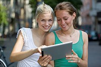 Germany, North Rhine Westphalia, Cologne, Young women using digital tablet, smiling
