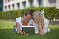 Germany, North Rhine Westphalia, Cologne, Young students with digital tablet, smiling