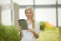 Germany, North Rhine Westphalia, Cologne, Young student with digital tablet, smiling, portrait