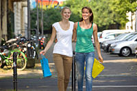 Germany, North Rhine Westphalia, Cologne, Young women with shopping bags on street, smiling