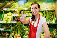 Germany, Cologne, Young woman showing thumbs up in supermarket, smiling, portrait (thumbnail)