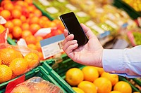 Germany, Cologne, Mature man using smart phone in supermarket (thumbnail)