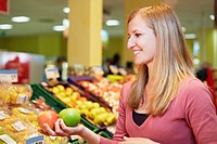 Germany, Cologne, Young woman comparing apples in supermarket