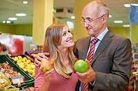 Germany, Cologne, Man and woman with apple and pear in supermarket, smiling