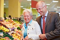 Germany, Cologne, Mature couple in supermarket, smiling