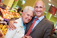 Germany, Cologne, Mature couple in supermarket, smiling, portrait