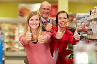 Germany, Cologne, Man and women showing thumbs up in supermarket (thumbnail)