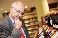 Germany, Cologne, Mature man inspecting wine in supermarket