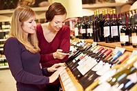 Germany, Cologne, Young women inspecting wine in supermarket