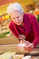 Germany, Cologne, Mature woman with raspberries and loupe in supermarket