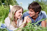 Germany, Cologne, Young couple lying in meadow, smiling